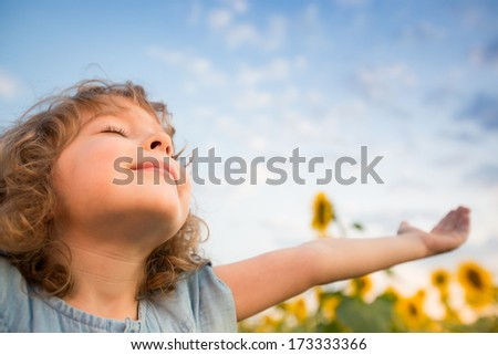 Happy child outdoors in spring sunflower field - stock photo