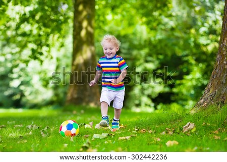Happy child playing European football outdoors in school yard. Kids play soccer. Active sport for preschool child. Ball game for young kid team. Boy scores a goal in football match. - stock photo