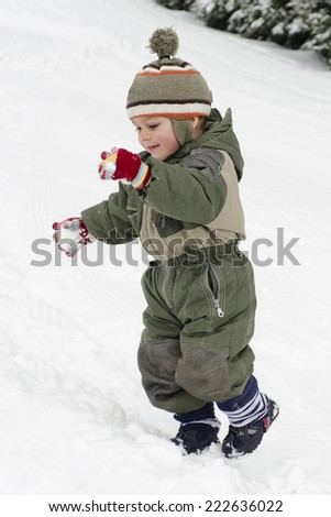 Happy child playing in fresh snow in winter.  - stock photo