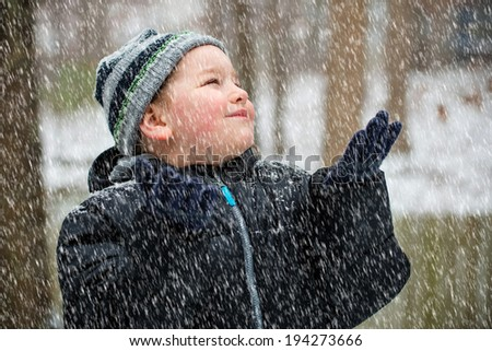 Happy child playing in the snow on winter day  - stock photo