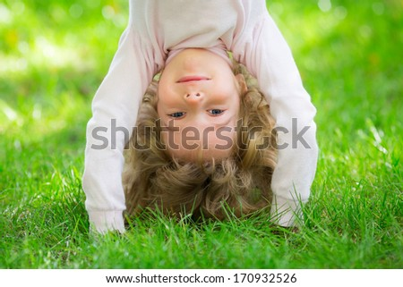 Happy child playing on green grass in spring park - stock photo