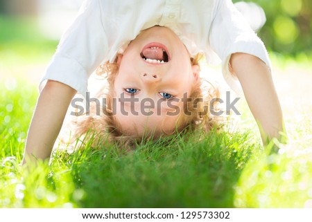 Happy child playing on green grass outdoors in spring park - stock photo
