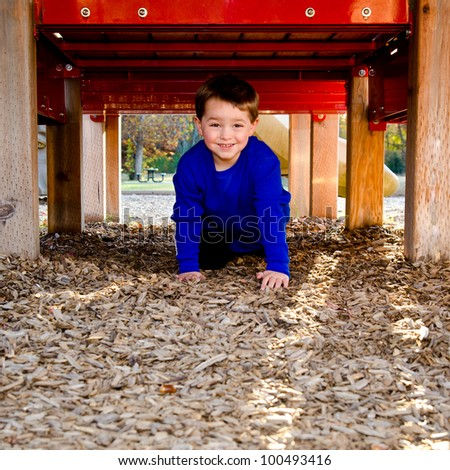 Happy child playing on playground - stock photo