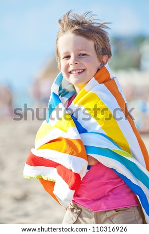 Happy child playing on the beach in summer