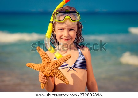 Happy child playing on the beach. Kid holding starfish. Summer vacations concept - stock photo