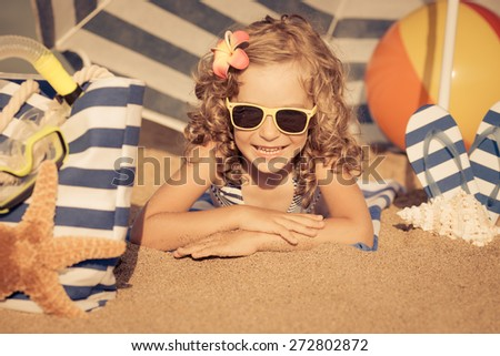 Happy child playing on the beach. Kid lying on sand. Summer vacations concept. Toned image - stock photo