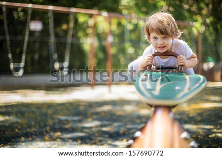 Happy child playing seesawing in playground - stock photo