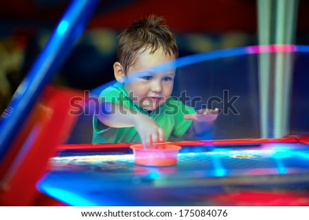 happy child playing table air hockey at fair - stock photo