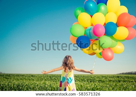 Happy child playing with balloons outdoor. Kid having fun in spring field
