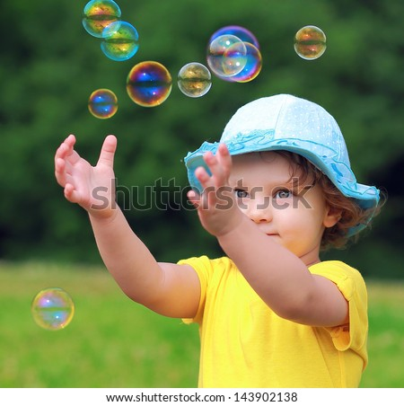 Happy child playing with bubbles on summer background. Closeup portrait