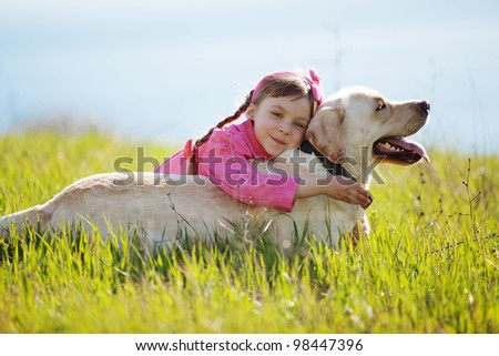 Happy child playing with dog in green field - stock photo