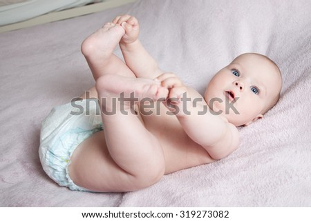 happy child playing with legs lying on the back - stock photo