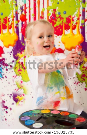 Happy child playing with paints
