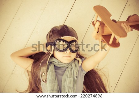 Happy child playing with toy airplane. Kid lying on wooden floor at home. Retro warm toned - stock photo
