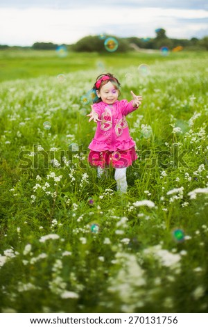 Happy child. Portrait of little girl playing with bubbles against green background. Spring or summer time. Cheerful carefree kid playing outside. Happy smiling laughing kid - stock photo