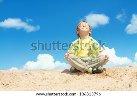 Happy Child Positive Think, Boy Sitting in Yoga Lotus position over blue sky on the top. Kid  Happiness concept. - stock photo