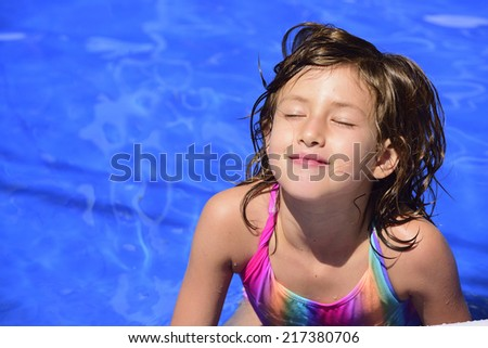 Happy child relaxing in the pool sunbathing with eyes closed and copyspace - stock photo