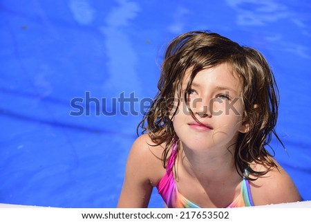 Happy child relaxing in the pool with copyspace