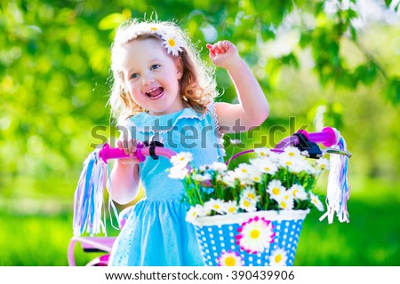 Happy child riding a bike. Cute kid biking outdoors. Little girl in a blue dress on a pink bicycle with daisy flowers in a basket. Healthy preschool children summer activity. Kids playing outside. - stock photo