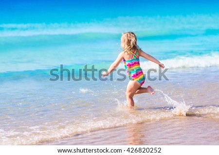 Happy child running and jumping in the waves during summer vacation on exotic tropical beach. Holiday on ocean coast for family with young children. Kids play at the sea. Little girl learning to swim. - stock photo