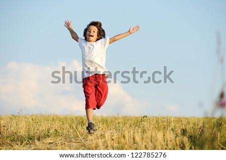Happy child running on beautiful field - stock photo