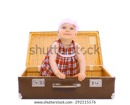 Happy child sitting in a suitcase playing and having fun - stock photo