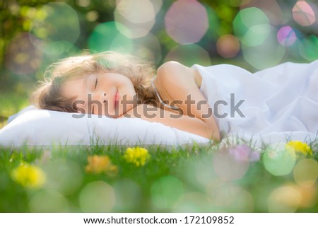 Happy child sleeping on green grass outdoors in spring garden - stock photo