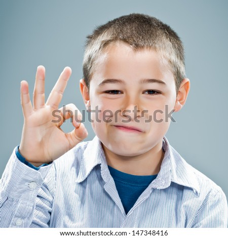 Happy Child Smiling Doing OK Sign Over a Grey Background - stock photo