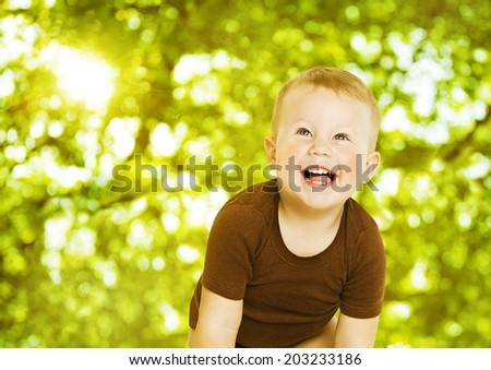 Happy child smiling over green background. Close up baby portrait. - stock photo