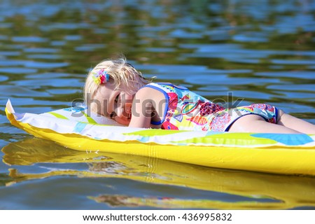 Happy child swimming in the lake. Healthy smiling toddler girl relaxing in the water on inflatable toy mattress. Active summer vacation concept. - stock photo