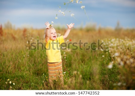 happy child throwing up flowers   - stock photo
