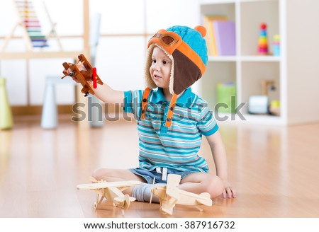 happy child toddler playing with toy airplane and dreaming of becoming a pilot - stock photo