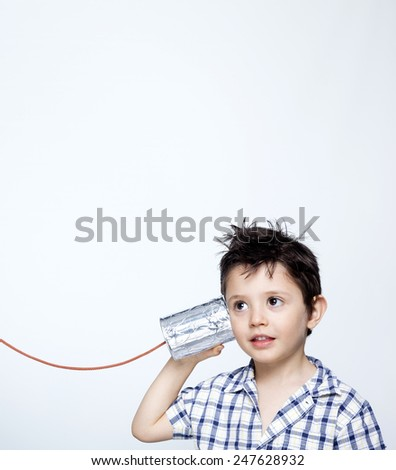 Happy child using a can as telephone against gray background - stock photo
