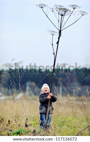 Happy child walking in autumn field. A boy plays with a long stick. - stock photo