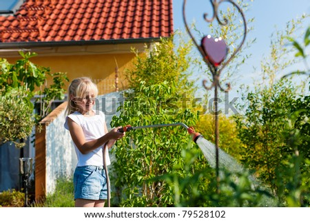 Happy child watering flowers in the garden in front of her family home - stock photo