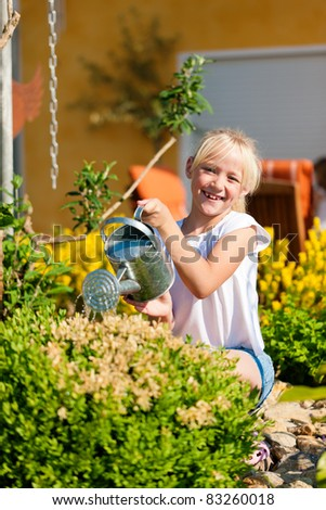 Happy child watering flowers in the garden in front of her home - stock photo