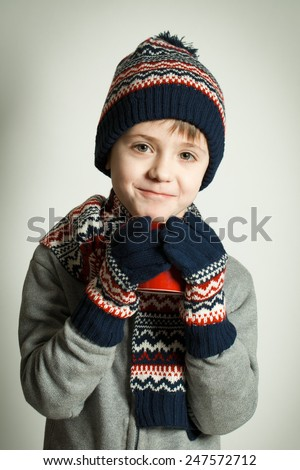 Happy child wearing a woolen hat and scarf drinking hot tea - stock photo