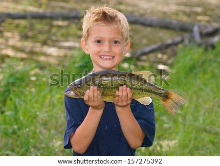 Happy child with a big fish he caught next to a pond - stock photo