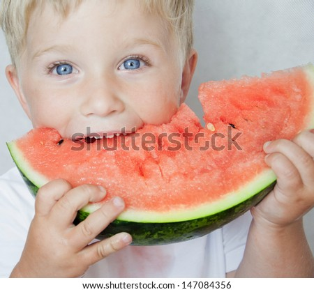 Happy child with big red slice of watermelon on grey background - stock photo