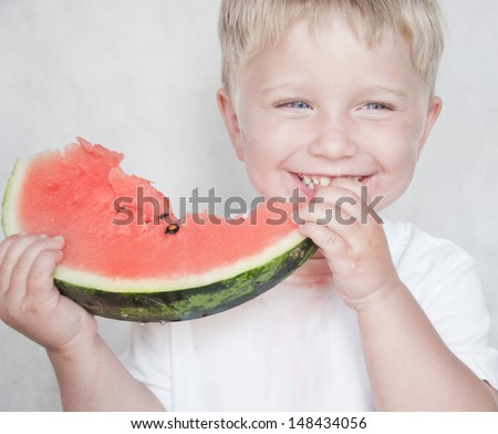 Happy child with big red slice of watermelon on grey background