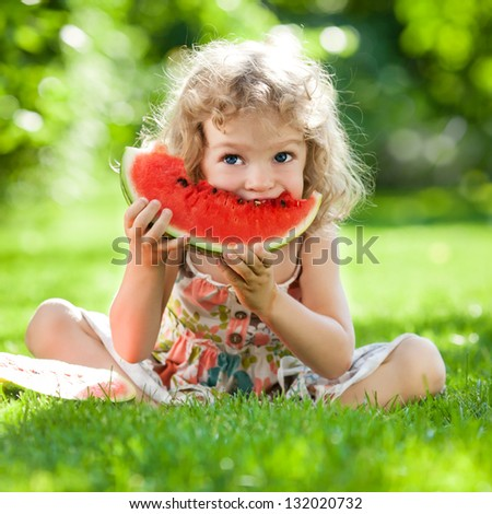 Happy child with big red slice of watermelon sitting on green grass in summer park. Healthy eating concept