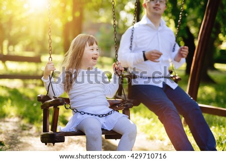 Happy child with down syndrome enjoying swing on playground - stock photo