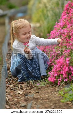 Happy child with flower outdoors in spring garden - stock photo