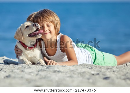 Happy child with her dog - stock photo