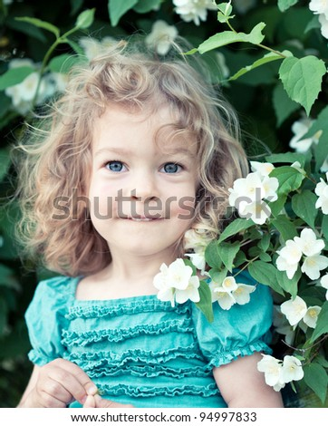Happy child with jasmine flowers outdoors in spring park - stock photo