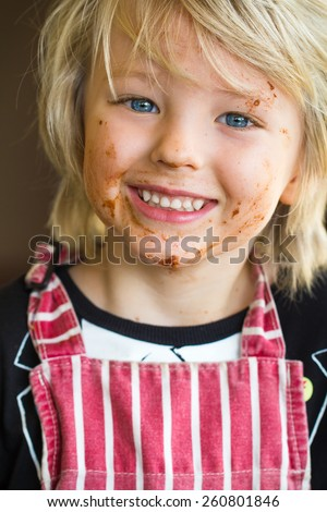 Happy child with messy chocolate face from baking - stock photo