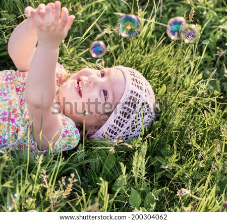 happy child with soap bubbles outdoor