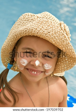 Happy child with sunscreen on my face against the background of water - stock photo