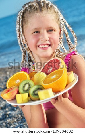 Happy child with tropical fruit on the beach - stock photo