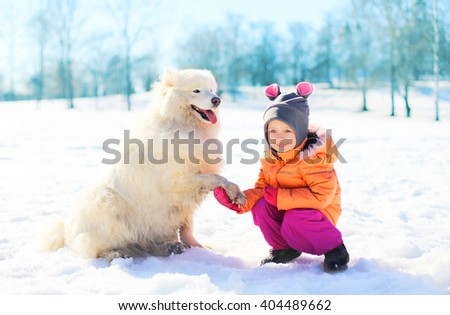 Happy child with white Samoyed dog on snow in winter park - stock photo